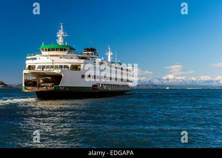 Washington State Ferry with snowy mountains of Olympic Peninsula in the background, Seattle, Washington, USA - Stock Photo