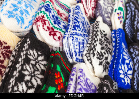 Colorful woolen mittens lie on the market counter - Stock Photo