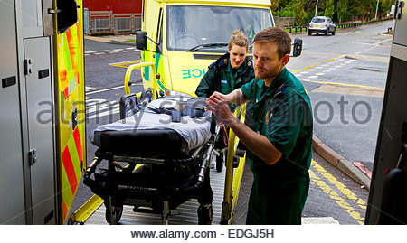 Male and female paramedics loading an empty stretcher trolley into an NHS Ambulance in north west England UK - Stock Photo