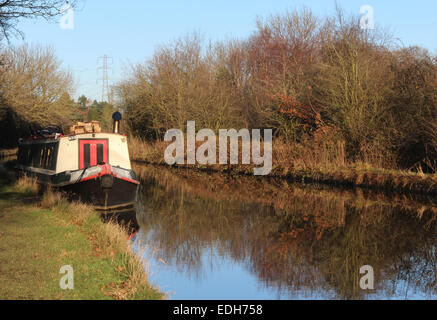 Canal boat moored on the Macclesfield canal near Adlington Cheshire in late afternoon winter sun with tree reflections. - Stock Photo