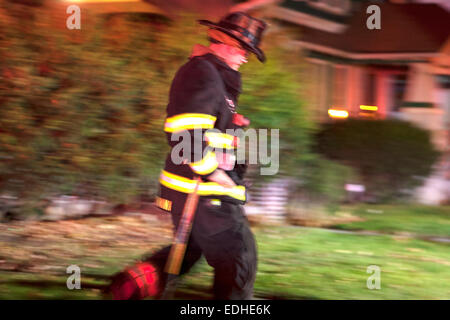 Milwaukee Fire Department MFD firefighter blurred running on scene of a Milwaukee house fire - Stock Photo