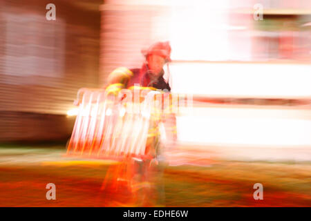 Firefighter carrying a ladder from a scene of Milwaukee house fire blurred with motion - Stock Photo