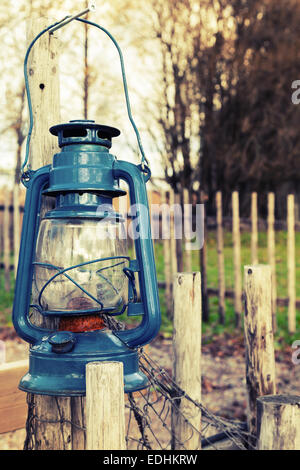 Old blue kerosene lamp hangs on wooden outdoor fence, vintage toned photo with filter effect - Stock Photo