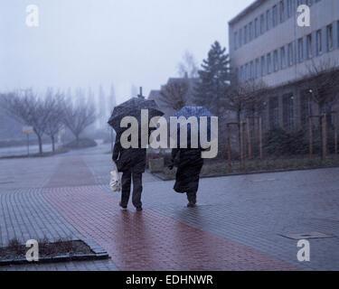weather, bad weather, rain, sleet, windy, storm, misty, elder couple on a sidewalk, man and woman, winter clothing, - Stock Photo