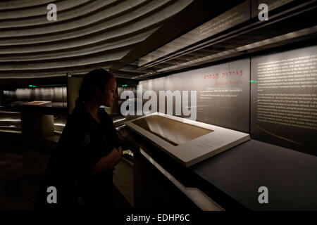 An Israeli soldier inspecting an ancient manuscript of Dead Sea Scrolls displayed inside the 'Shrine of the Book' - Stock Photo
