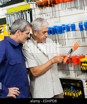 Customer Examining Packed Screwdriver While Vendor Looking At - Stock Photo