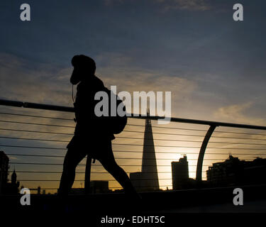 London 7th January 2015. Clear UK weather and beautiful sunrise. Commuters walk to work over the Millennium Bridge - Stock Photo