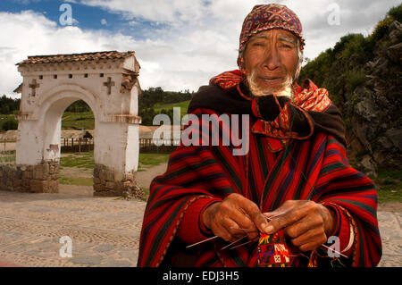 An artisan weaves a hat on the streets of Chinchero in the Sacred Valley near Cuzco. Chinchero is a small Andean - Stock Photo