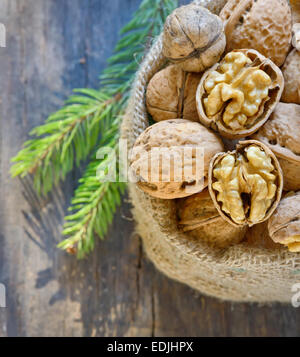 Christmas decoration with dried walnut in sack and pine tree twigs - Stock Photo