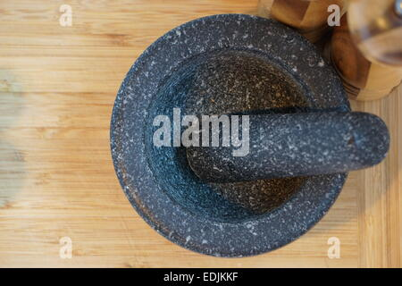 Mortar and pestle on wooden chopping board. - Stock Photo