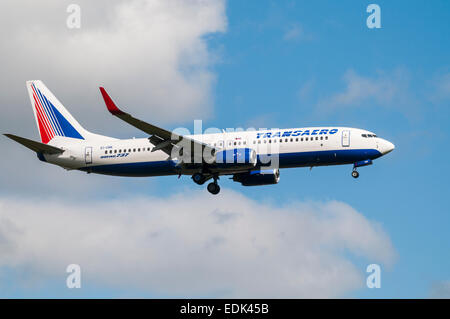 Side view of a Transaero Boeing 737 aeroplane coming in to land - Stock Photo