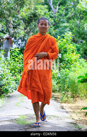 Young Buddhist Monk Walking And Smiling To The Camera - Stock Photo