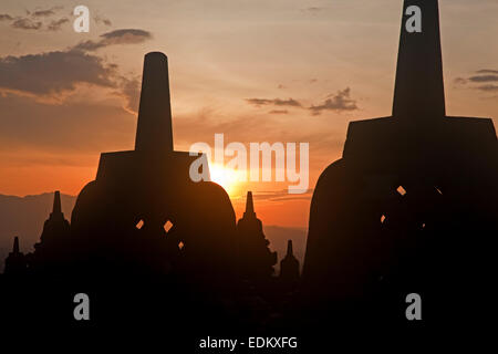 Silhouetted stupas of Borobudur / Barabudur, 9th-century Mahayana Buddhist Temple at sunset in Magelang, Central - Stock Photo