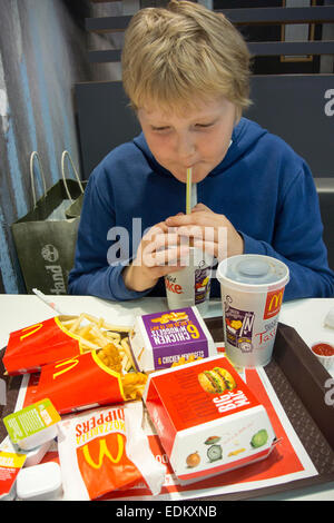 Young boy eating at a fast food resturant, UK. - Stock Photo