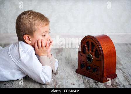 Cute boy of five years listening to Vintage Radio - Stock Photo