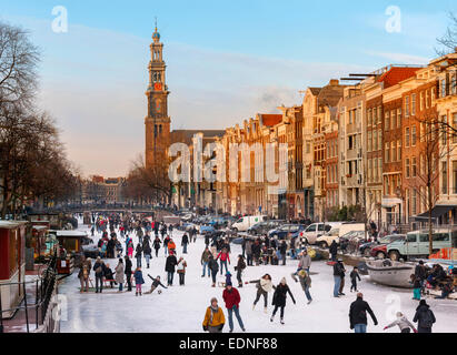 Amsterdam Ice Skating on a frozen Canal in winter. Prinsengracht Canal with Westertoren Tower and Westerkerk - Stock Photo