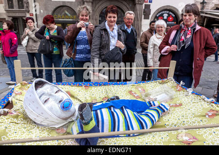 Street performer dressed up as baby in a crib, People Old Town Square, Prague, Czech Republic - Stock Photo