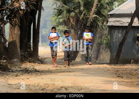 Dhaka 08 January 2015. Three neighboring school-boy on their way to school. - Stock Photo