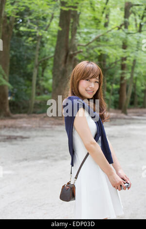 A woman in a Kyoto park posing for a photograph. - Stock Photo