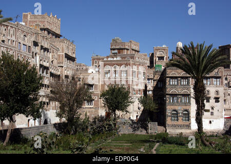 Traditional houses look on to a garden in the old town of Sanaa, Yemen - Stock Photo