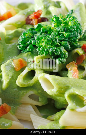 A close up of penne pasta and pesto sauce and bacon and broccoli topping - Stock Photo