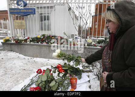 Moscow, Russia. 8th Jan, 2015. A woman leaves flowers outside the embassy of France in Moscow for the victims of - Stock Photo