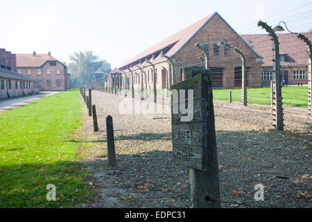 halt stop sign in front of blocks at the Auschwitz concentration camp, Auschwitz, Poland - Stock Photo