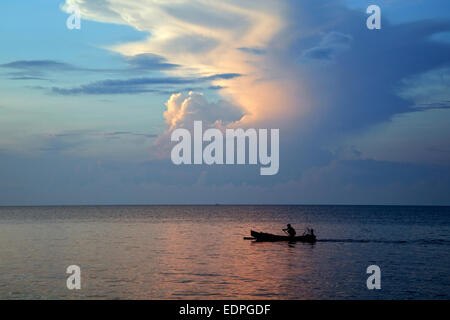 Fisherman in Indonesian jukung, traditional wooden outrigger canoe, paddling on the Indian Ocean at sunset, Java, - Stock Photo