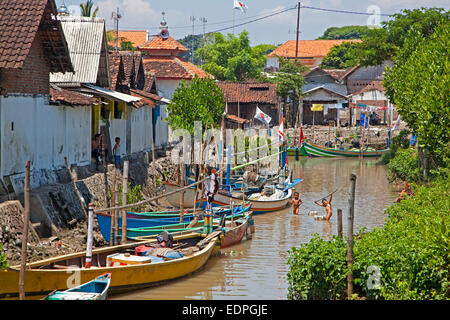 Traditional Indonesian wooden open fishing boats and children playing in dirty water at Probolinggo, East Java, - Stock Photo