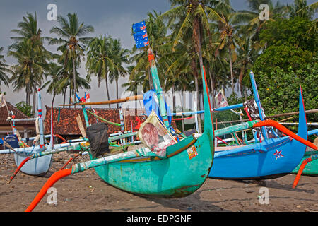Colourful Indonesian jukungs, traditional wooden outrigger canoes on the Madewi beach along the Indian Ocean, Bali, - Stock Photo