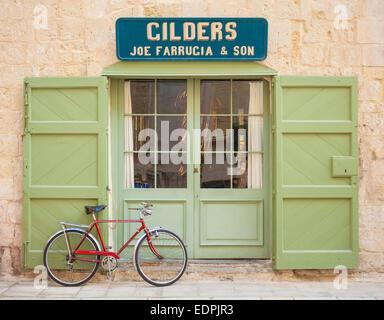 Retro Red Bicycle outside Green doors of traditional Gilders shop Mdina Malta EU Europe - Stock Photo