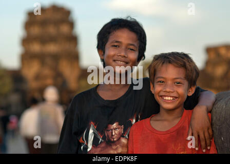 Portrait of two boys in front of the faces of the Bayon temple. Angkor Thom. We stand before it stunned. It is like - Stock Photo