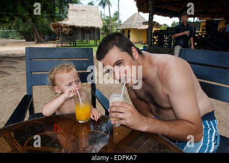 Taking breakfast in Beach on the island of Koh Russei. Cambodia. Travel with children's. Father traveling with her - Stock Photo