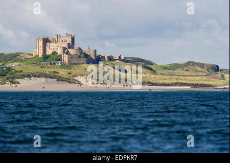 A view from the Farne Islands looking back at coastline with the beach and Bamburgh Castle in Northumberland - Stock Photo