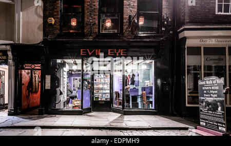 The 'Evil Eye' bar pub off licence and internet cafe on Stonegate in York, UK. Shot at night. - Stock Photo