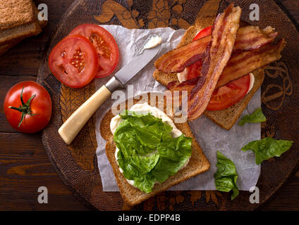 A delicious BLT bacon, lettuce, and tomato sandwich on rustic tabletop. - Stock Photo