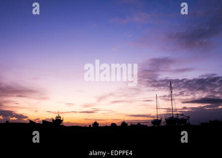 Fishing / sailing boats on dry land at sunrise in the harbour at Lindisfarne, Holy Island, Northumberland, England. - Stock Photo