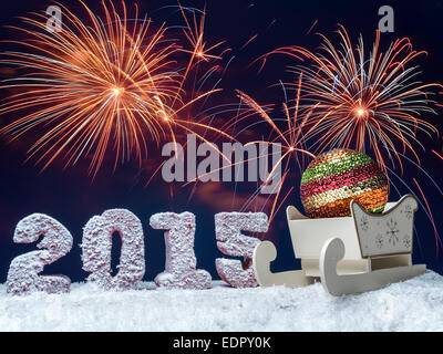 Frosted 2015 New Year digits and big glistering ball in wooden sleigh over dark blue sky with fireworks - Stock Photo