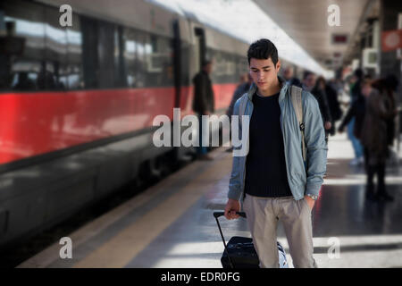 Handsome young male traveler in train station - Stock Photo