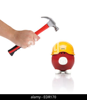 Piggy with hard hat stops him from being smashed by a hammer - Stock Photo