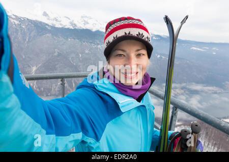 Female skier taking selfie. - Stock Photo