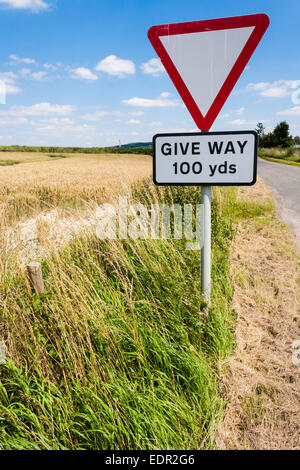 Give Way Sign by field on rural road in England. - Stock Photo