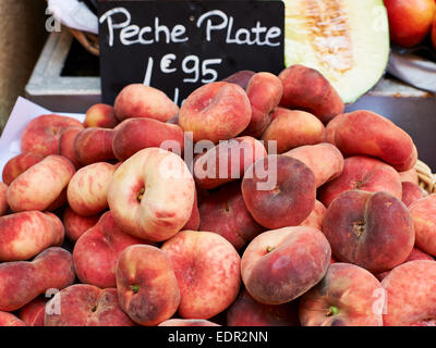 Red ripe flat peaches for sale on market stall in Provence, South France - Stock Photo