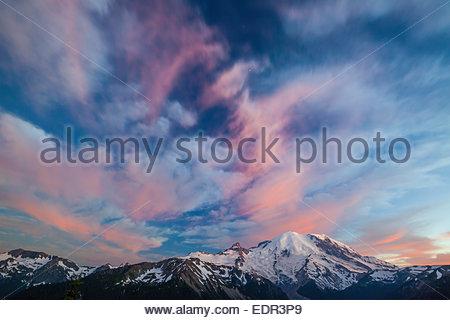 Alpenglow illuminates the clouds above Mount Ranier in Mount Ranier National Park. - Stock Photo