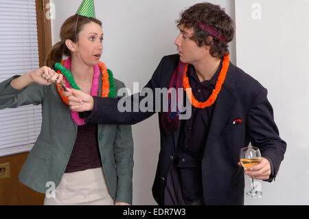 A woman at an office party taking car keys away from a disheveled looking man who has been drinking alcohol. - Stock Photo