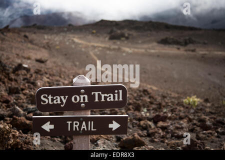 A sign telling hikers to stay on the trail in Haleakala crater. Hiking off-trail leads to significant soil erosion - Stock Photo
