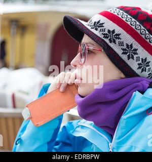Woman in ski resort using smartphone. - Stock Photo