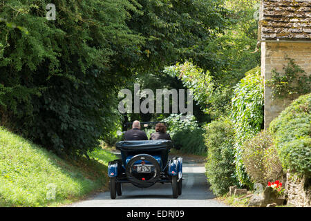 Well-preserved veteran Model T Ford auto touring along country lane in The Cotswolds, UK - Stock Photo