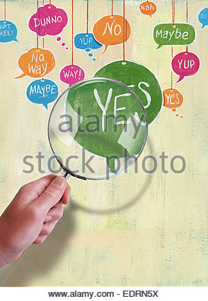 Hand holding magnifying glass over yes, no, maybe speech bubbles - Stock Photo