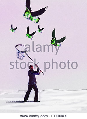 Businessman chasing flying dollars with net - Stock Photo